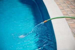 pool dilution, drain pool, refill pool, pool hose, chemical accumulation in pools, orenda, shutterstock